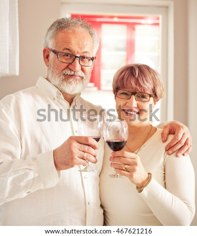 Photo of beautiful senior couple,they  toasting  with  glass of red wine.