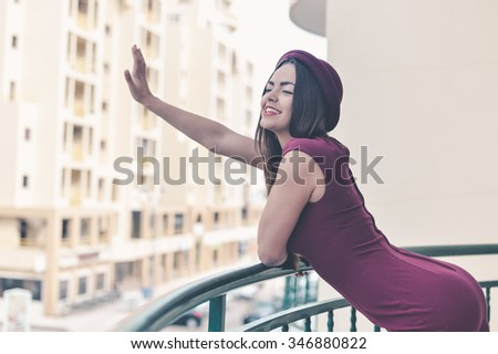 Photo of beautiful smiling woman in elegant dark red dress and hat standing on balcony waving her hand on modern building background  - stock photo
