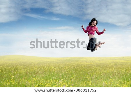 Photo of beautiful young Asian woman jumping on the meadow at springtime - stock photo