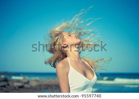 Photo of beautiful young blonde at blue sea - stock photo