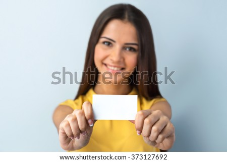 Photo of beautiful young business woman standing near gray background. Woman with yellow shirt looking at camera, smiling and showing visit card. Focus on visit card - stock photo