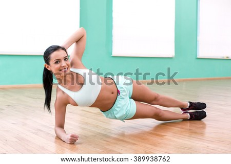 Photo of beautiful young sporty woman. Fitness girl doing plank in sport club. Woman smiling and looking at camera