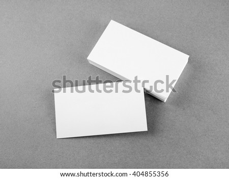 Photo of blank business cards on gray background. Mock-up for branding identity. For design presentations and portfolios. Top view. Grayscale image. - stock photo