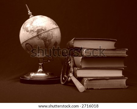 Photo of books with magnifying glass and candle