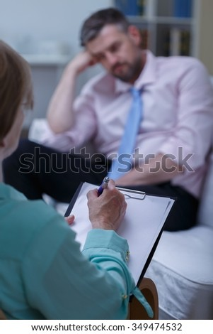 Photo of bored man during psychological test - stock photo