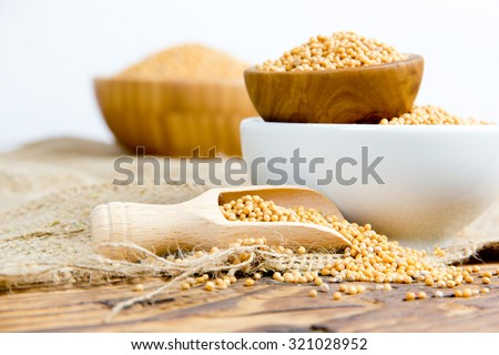 Photo of bowls and wooden spoon full of mustard seeds on burlap and wooden board