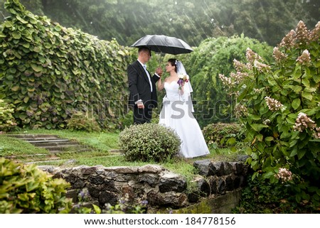 Photo of bride and groom under black umbrella at park - stock photo