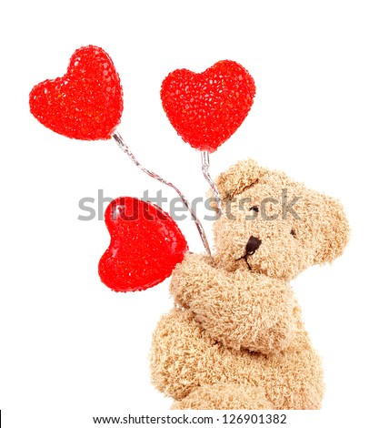 Photo of brown teddy bear holding red heart-shape balloons, closeup portrait of sweet fluffy soft toy isolated on white background, romantic gift for Valentines day, cute present for love holiday - stock photo
