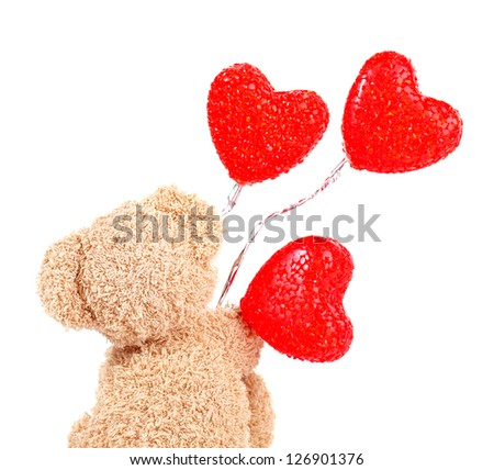 Photo of brown teddy bear holding red heart-shape balloons, rear view of sweet fluffy soft toy isolated on white background, romantic gift for Valentines day, cute present for love holiday - stock photo