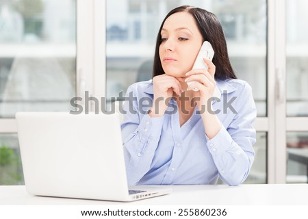 Photo of brunette businesswoman phoning while looking to the notebook in office - stock photo