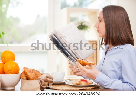 Photo of brunette businesswoman reading the newspaper while having breakfast at home - stock photo