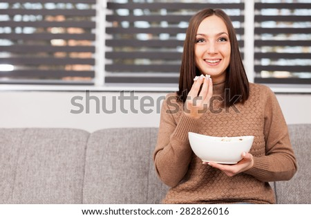 Photo of brunette caucasian woman eating popcorn while looking tv at home - stock photo