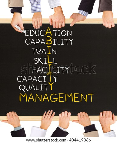 Photo of business hands holding blackboard and writing ABILITY MANAGEMENT concept - stock photo