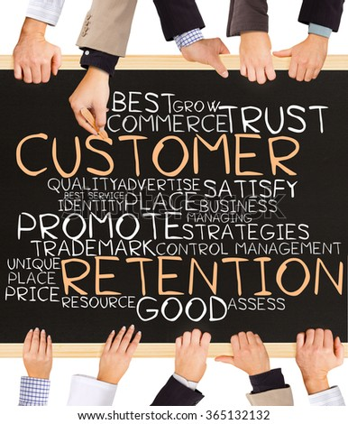 Photo of business hands holding blackboard and writing CUSTOMER RETENTION concept - stock photo