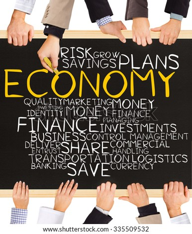 Photo of business hands holding blackboard and writing ECONOMY word cloud - stock photo