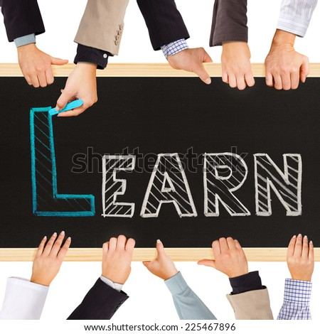 Photo of business hands holding blackboard and writing LEARN concept - stock photo