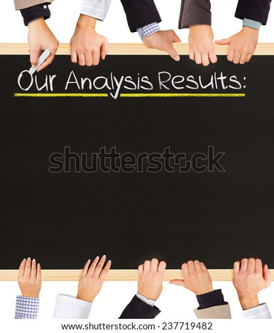 Photo of business hands holding blackboard and writing Our Analysis Results - stock photo