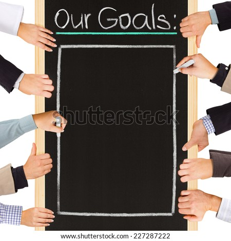 Photo of business hands holding blackboard and writing OUR GOALS - stock photo