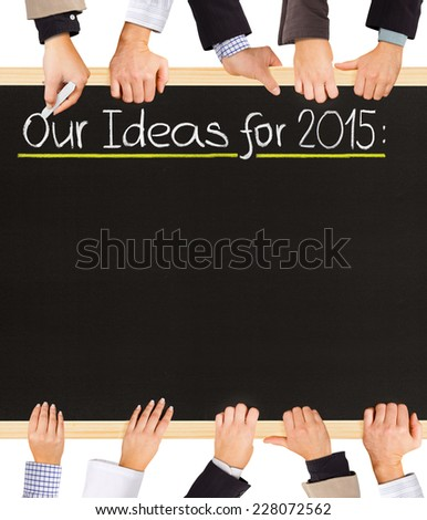 Photo of business hands holding blackboard and writing Our Ideas for 2015 - stock photo