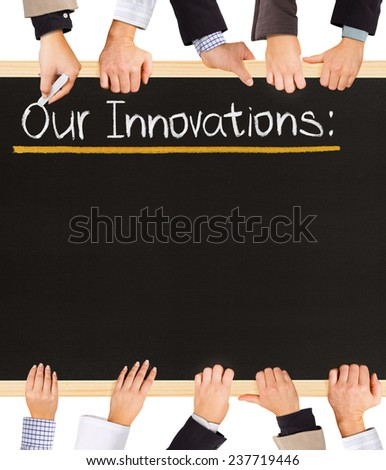 Photo of business hands holding blackboard and writing Our Innovations - stock photo