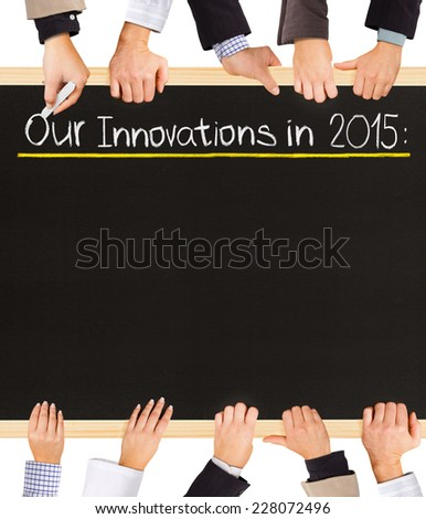 Photo of business hands holding blackboard and writing Our Innovations for 2015 - stock photo
