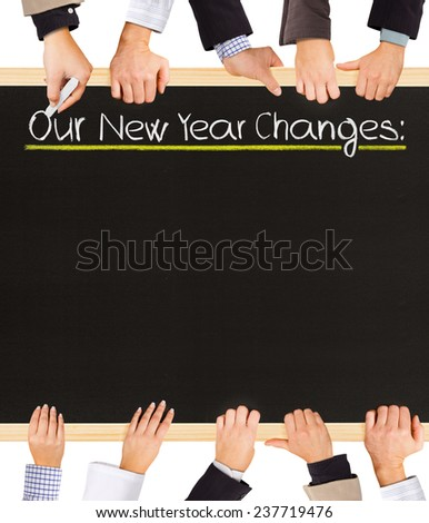 Photo of business hands holding blackboard and writing Our New Year Changes - stock photo
