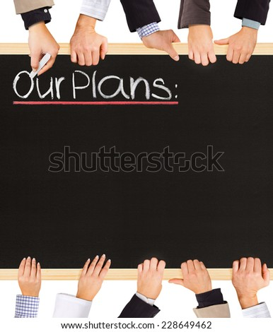 Photo of business hands holding blackboard and writing Our Plans - stock photo
