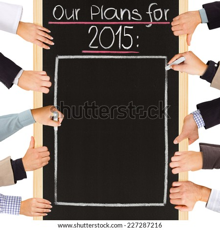 Photo of business hands holding blackboard and writing PLANS for 2015 - stock photo