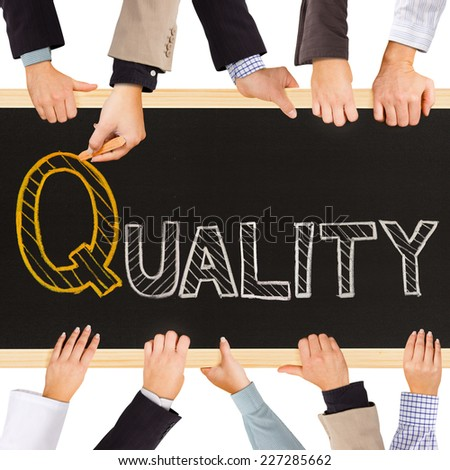 Photo of business hands holding blackboard and writing QUALITY concept - stock photo