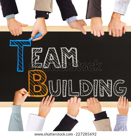 Photo of business hands holding blackboard and writing TEAM BUILDING concept - stock photo