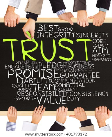 Photo of business hands holding blackboard and writing TRUST concept - stock photo