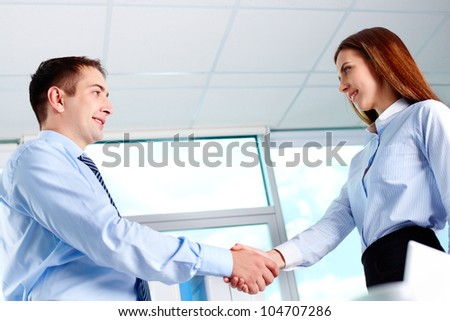 Photo of business partners handshaking after striking deal - stock photo