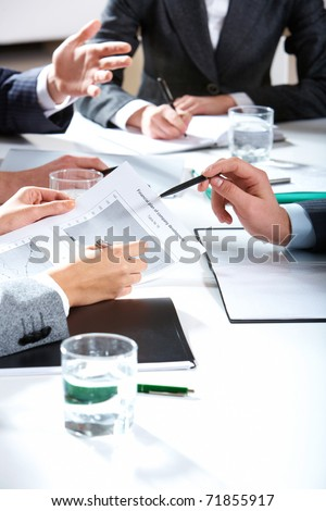 Photo of business people hands holding papers and pens over workplace - stock photo