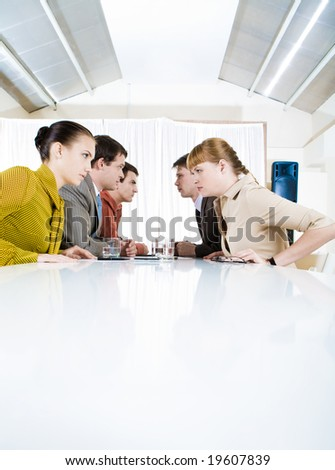 Photo of business people staring at each other with aggressive expression - stock photo