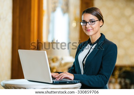 Photo of business woman in expensive hotel. Young business woman wearing suit and glasses, standing in nice hotel room, using laptop and looking at camera - stock photo