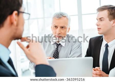 Photo of businessman and his colleagues. Businessmen working in office with big window. Men using laptop - stock photo