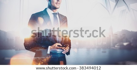 Photo of businessman holding smart phone. Double exposure photo of panoramic city view at sunrise  - stock photo