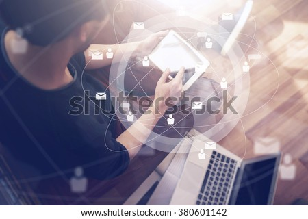 Photo of businessman touching screen Of generic design tablet holding in his hands. Laptop on the floor. Digital interface effect. Horizontal mockup - stock photo