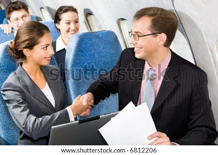Photo of businessmen and businesswoman shaking hands in a plane - stock photo