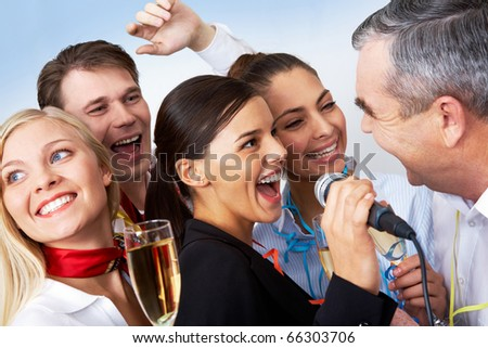 Photo of businesspeople singing Christmas songs at party