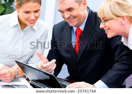 Photo of businessteam doing some computer work and looking at the laptop screen during meeting in the office - stock photo