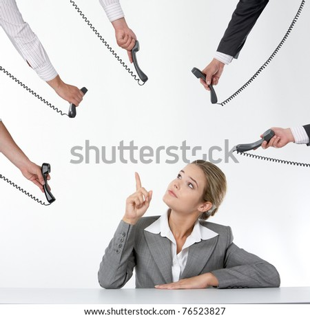 Photo of businesswoman pointing at telephone receiver while being offered several of them - stock photo