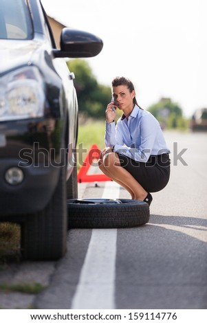 photo of businesswoman with flat tire - stock photo