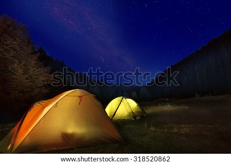 Photo of camp with glowing tents in front of milkyway night sky in the mountains - stock photo