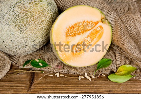 Photo of cantaloupe melon with slice and leaves on burlap and wooden board - stock photo