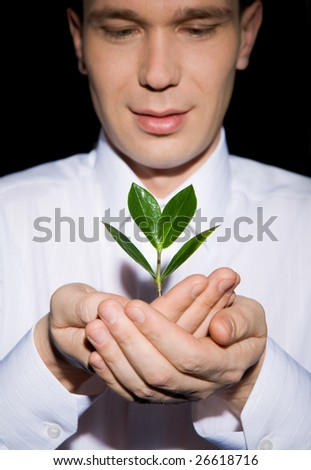 Photo of careful man holding fresh sprout and looking at it
