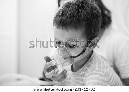 photo of caring mother and kid curing illness with aerosols inhalation - stock photo
