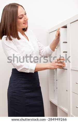 Photo of caucasian brunette businesswoman sorting her documents in the cupboard - stock photo