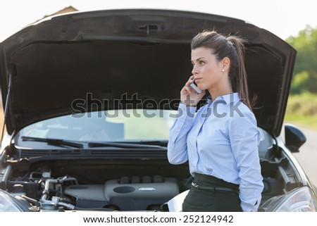 Photo of caucasian businesswoman standing next to her car and calling assistance for car problems - stock photo