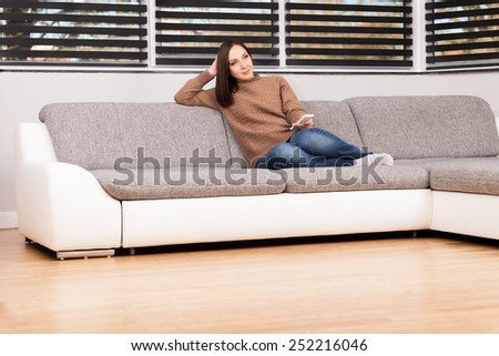 photo of caucasian young woman sitting on a sofa while looking tv - stock photo